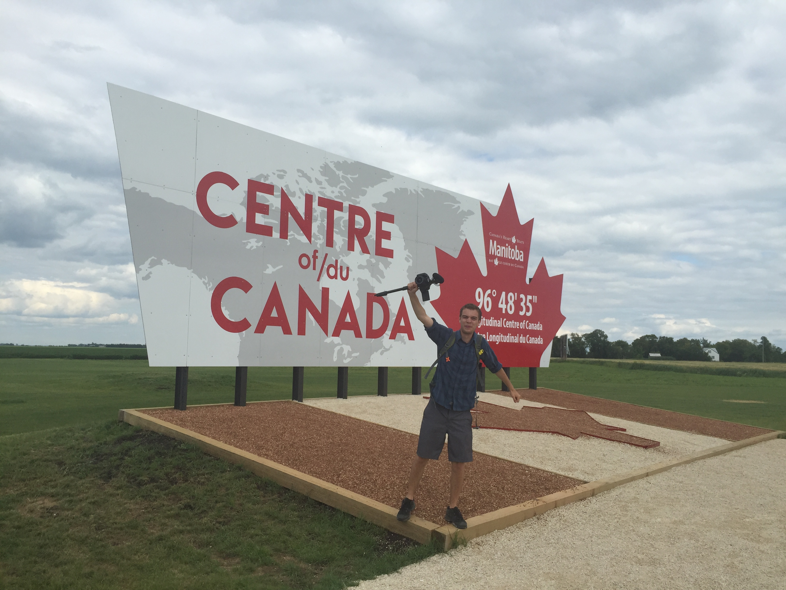 "Jimmy Chabot with his camera, posing in front of the ""Centre of/du Canada"" poster"