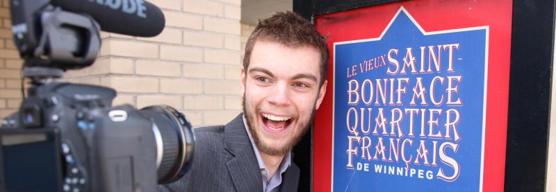 "Jimmy Chabot with his camera, posing in front of the ""Le vieux Saint-Boniface, quartier français de Winnipeg"" poster"