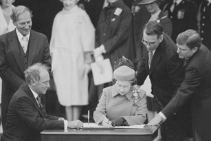 Her Majesty Queen Elizabeth II and the Prime Minister, the Rt. Hon. Pierre Elliott Trudeau signing the Constitution.